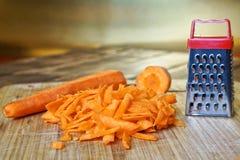 Заскрежетанная морковь лежит в кухне, на винтажной деревянной разделочной доске Необыкновенные тайна и обман зрения стоковые фото