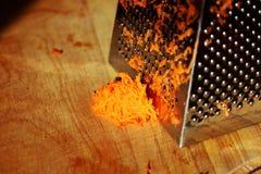 Заскрежетанная склонность моркови на стальной терке Стоковые Фотографии RF