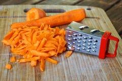 Заскрежетанные моркови на деревянной поверхности Необыкновенные тайна и обман зрения стоковые фотографии rf