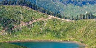 Засохлость на наклоне горы на голубое озеро стоковые изображения