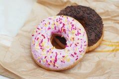 2 застекленных Donuts лежа на предпосылке бумаги ремесла Сладостный десерт для завтрака Стоковое Изображение RF