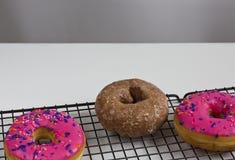 3 застекленных Donuts на шкафе выпечки Стоковые Фотографии RF