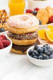 Застекленные donuts, помадки и свежие ягоды на белой таблице, вертикальной Стоковые Фотографии RF