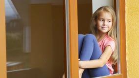 Застенчивая девушка сидя окном, смотря улицу и развевая приветствия к кто-то акции видеоматериалы