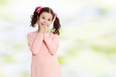 Застенчивая девушка держа руки около стороны Стоковая Фотография