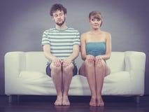 Застенчивая женщина и человек сидя близко к одину другого на кресле Стоковое Изображение