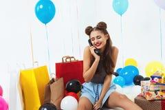 Застенчивая и милая девушка сидя при подарки на день рождения получая желания Стоковое фото RF