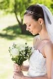 Застенчивая невеста держа букет в саде Стоковое Изображение