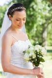 Застенчивая невеста держа букет цветка в саде Стоковые Фотографии RF