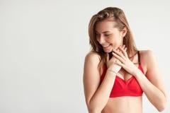 Застенчивое брюнет в красном бюстгальтере sportswear смотря к стороне на космосе экземпляра Стоковые Изображения