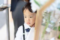 Застенчивый мальчик ждет его мать в церков с официальным костюмом стоковая фотография rf