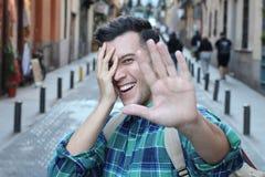Застенчивый человек покрывая его сторону пока усмехающся стоковые изображения rf