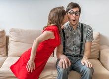 Застенчивый человек удивлен поцелуем от женщины сидя на софе Концепция датировка стоковая фотография rf