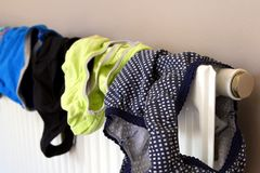 Засыхание нижнего белья на отечественном радиаторе после быть помытым стоковое изображение rf
