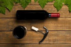 Затворы стекла консервооткрывателя бутылки вина и листья лозы на деревянной предпосылке Взгляд сверху с космосом экземпляра стоковое фото