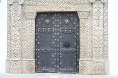 Затейливая каменная кладка обрамляет большую дверь металла в Антигуе Гватемале Стоковые Изображения
