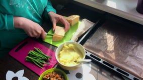 Женщина режет сыр на разделочной доске Затем на плите зеленый лук, картофельные пюре и зажаренные грибы видеоматериал