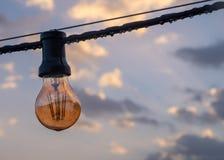 Затмите электрическую лампочку на облачном небе стоковое изображение