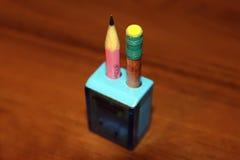 Заточенные карандаши в голубой точилке для карандашей на коричневой таблице Стоковое фото RF