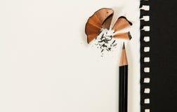 Заточите карандаш на белом столе Кроме черной бумаги стоковое фото