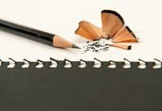Заточите карандаш на белом столе С черной бумагой стоковая фотография rf