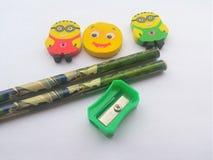 Заточник, карандаши и ластики на белой предпосылке Стоковые Фотографии RF