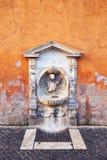 Затрапезный каменный фонтан в стене Стоковые Фото