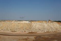 Затяжелитель backhoe, backhoe затяжелителя, землекоп на куче песка и камни на естественной предпосылке Стоковое Изображение