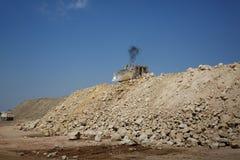 Затяжелитель backhoe, backhoe затяжелителя, землекоп на куче песка и камни на естественной предпосылке Стоковая Фотография