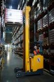 Затяжелитель склада используя платформу грузоподъемника стоковые фотографии rf