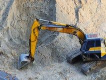 Затяжелитель экскаватора при rised backhoe стоя в песке стоковое фото rf