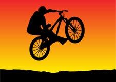 заход солнца велосипеда скача иллюстрация штока