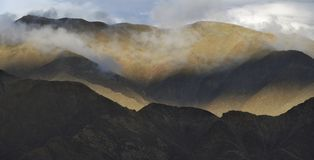 Заход солнца в горах: линии холмов гребня волнистые потеряны среди прозрачных белых облаков Стоковое Изображение RF