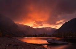 Заход солнца в горах Очаровательный ландшафт горы осени в красных тонах с небом захода солнца, рекой с отражением и сиротливой шл стоковые фотографии rf