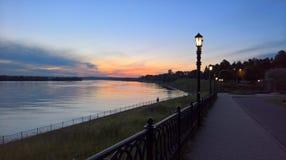 Заход солнца в городе региона Uglich Yaroslavl Взгляд обваловки Рекы Волга в зоне  стоковое фото
