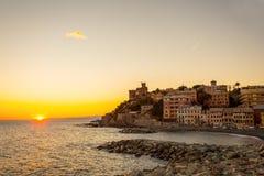 Заход солнца в деревне моря с заходом солнца Солнцем/домами цвета huoses//Генуей/Италией стоковая фотография