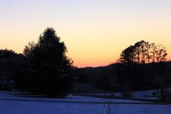 Заход солнца в зиме обрамленной красивыми деревьями стоковое изображение