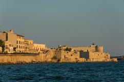 Заход солнца в обваловке острова Ortygia и Castello Maniace, Sy стоковые фото