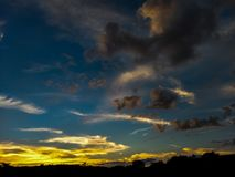 Заход солнца в позднем вечере с темными облаками, небе, солнце с интенсивными цветами стоковые изображения rf