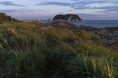 Заход солнца в Согвипхо с взглядом на острове маяка и луны, острове Jeju, Южной Корее Стоковая Фотография