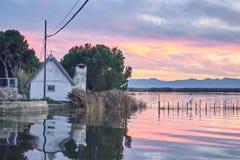 Заход солнца в спокойных водах Albufera de Валенсия, Испании Езда шлюпки в заходе солнца спокойных вод Albufera de стоковое изображение