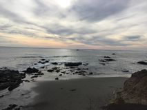 Заход солнца в Cayucos на пляже с утесами в волнах стоковое фото rf