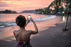 Заход солнца девушки фотографируя на пляже стоковое изображение