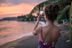 Заход солнца девушки фотографируя на пляже стоковая фотография