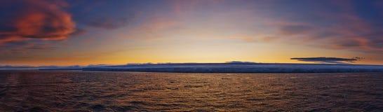 заход солнца замерли береговой линией, котор Стоковые Изображения