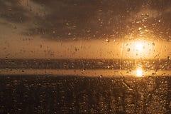 Заход солнца за ненастным окном стоковые изображения rf