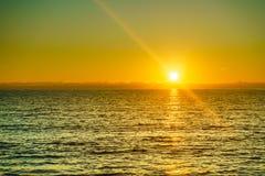 Заход солнца или восход солнца над поверхностью моря стоковые изображения