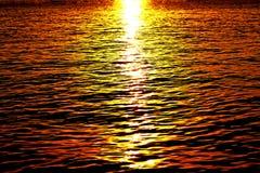 Заход солнца или свет восхода солнца на море с малыми волнами Стоковое фото RF