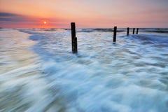 Заход солнца и волны Стоковые Изображения