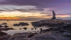 Заход солнца и маяк на море стоковое изображение